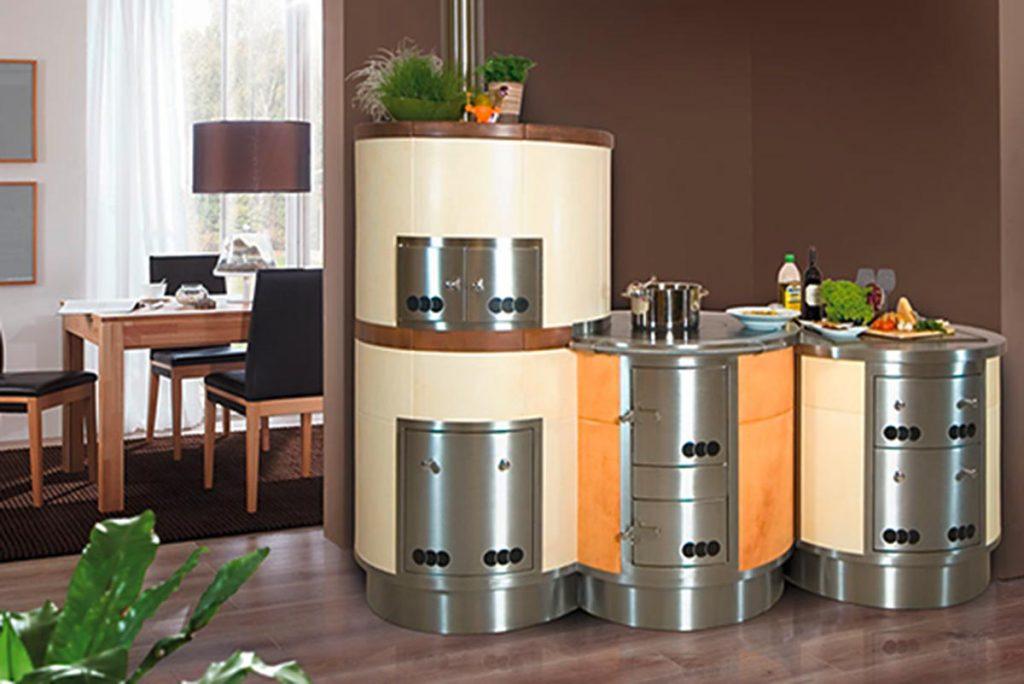 3-teiliger runder Holzherd mit Ceran-Kochfeld. In einen Nirosta-Herdrahmen können auch zB ein fugenlos eingeschweißtes Spülbecken sowie eine Arbeitsplatte aus Stein integriert werden.