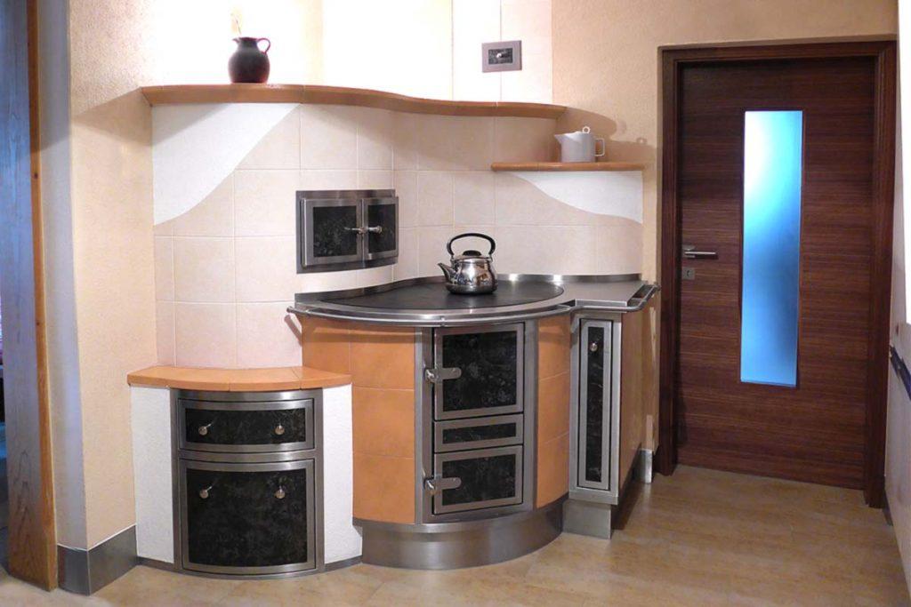 Runder Durchheizherd in Ecke mit Geschirrtuchauszug. Dieser Küchenherd hat eine Bestecklade sowie einen Holzwagen auf Schienen. Er heizt wahlweise auch den Kachelofen im Wohnzimmer dahinter.