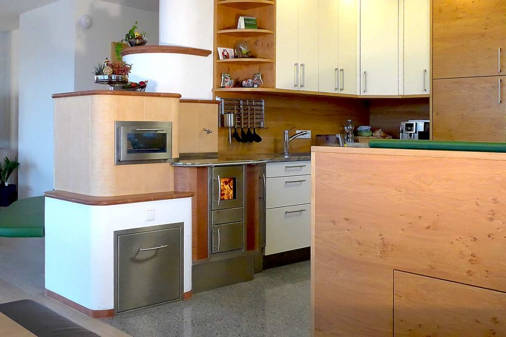 Kachelherd als Durchheizherd zum Kachelofen im Wohnzimmer, eingebaute Temperaturanzeige und Ofentüre mit Sichtfenster