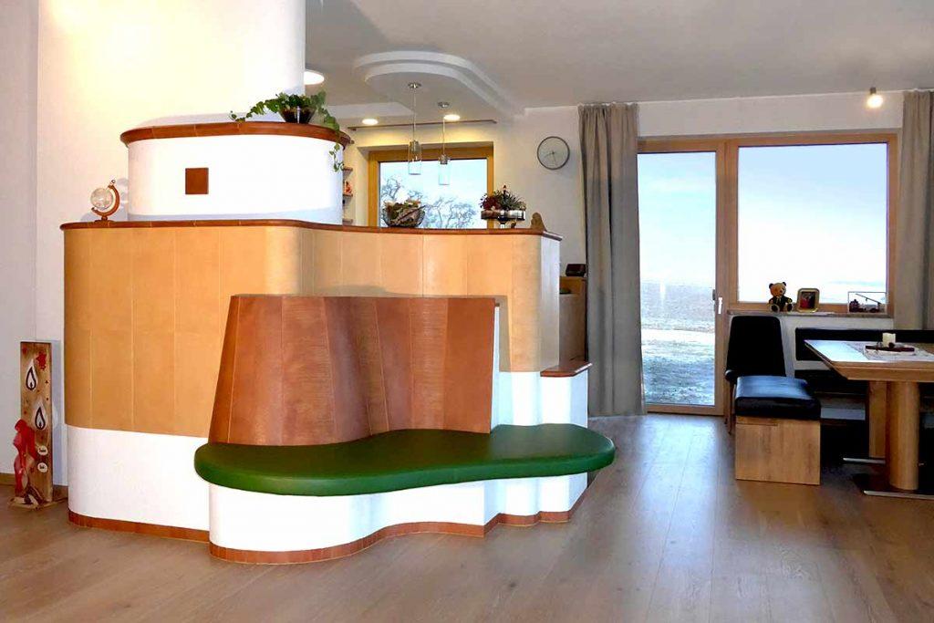Kachelofen im Wohnzimmer Außeneck mit schwebender Liegefläche dahinter ein Kachelherd