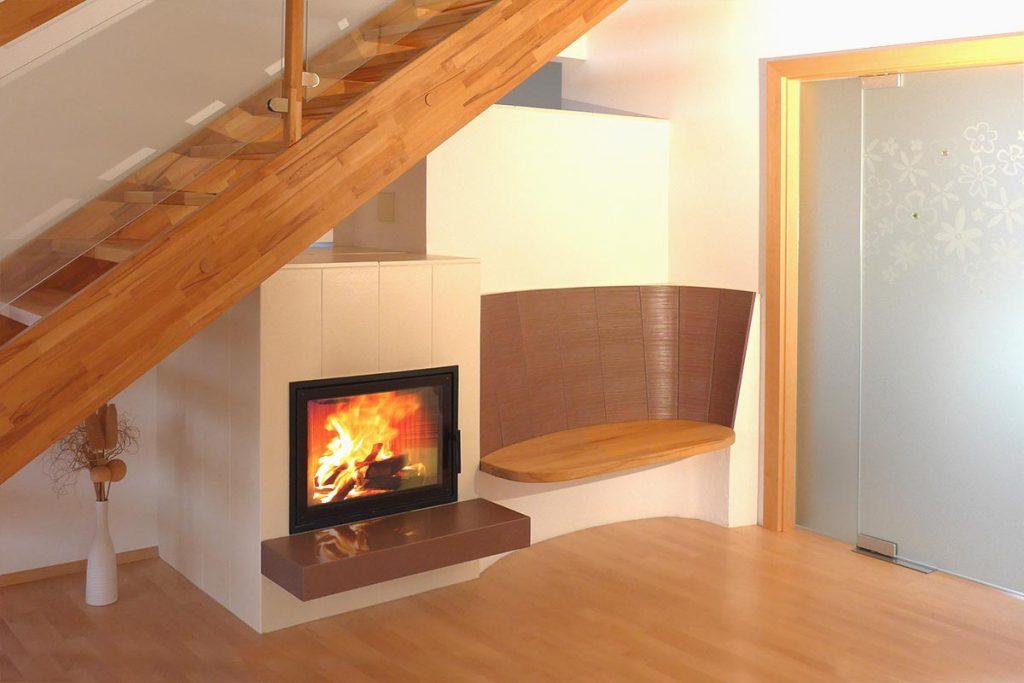 Kachelofen mit zwei Sichtfenstern und Liegefläche. Ein Tunnelofen hat zwei Sichtfenster und ist wahlweise von beiden Räumen aus zu befeuern und genießen.