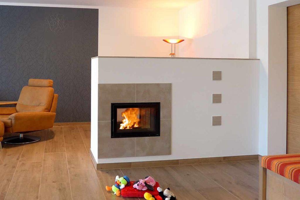 Tunnel- Kachelofen mit 2 Sichtfenstern für den Durchblick, moderne Idee als Raumteiler im Wohnzimmer