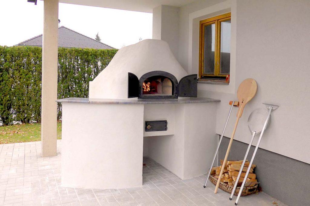 Ein gemauerter Brotback- und Pizzaofen auf einer Terrasse unter Dach. Ich Brennraum brennt schön das Feuer.