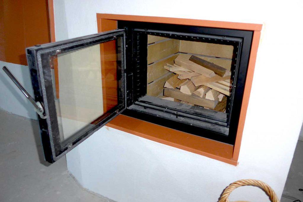 Brennholz kreuzweise geschichtet im Kachelofen Brennraum